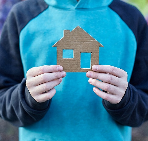 boy holding cardboard cut-out house