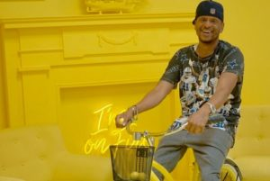 Project BOLT nonprofit co-founder Gemini Boyd on a bicycle in front of a yellow wall