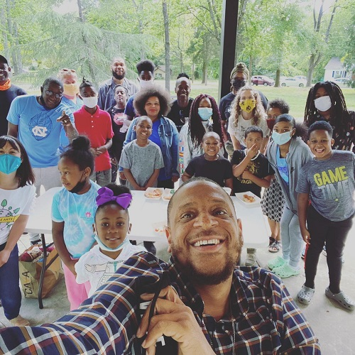 Project BOLT nonprofit co-founder Gemini Boyd takes a selfie with a group of kids outside